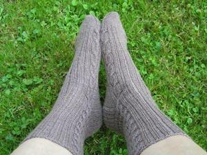 braune Socken mit Zopfmuster an Füssen