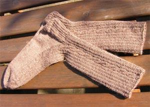 braune Socken mit Zopfmuster auf einem Holztisch