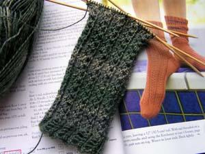 angefangene Socken auf den Nadeln in Dunkelgrün