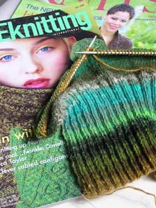 grüngestreiftes Strickstück auf grünen Strickzeitschriften