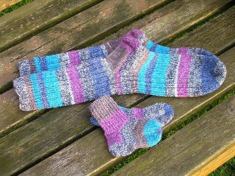 ein groߟes und ein kleines Paar Socken in blau, pink und braun geringelt