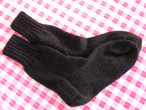 schwarze Socken auf rotweiߟkariertem Tischtuch