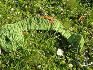 grünes Strickstück auf Wiese
