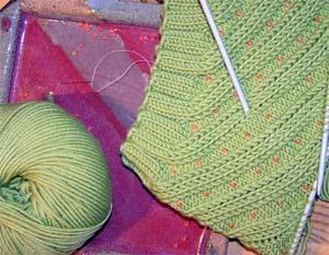 grünes Strickstück mit orangen Perlen