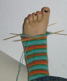 angefangener Sock auf Fuߟ mit Nadeln