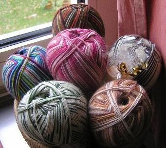 6 Knäuel Wolle in einem Korb am Fenster