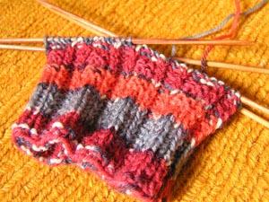 Socke auf Nadeln in rotgraugemustert