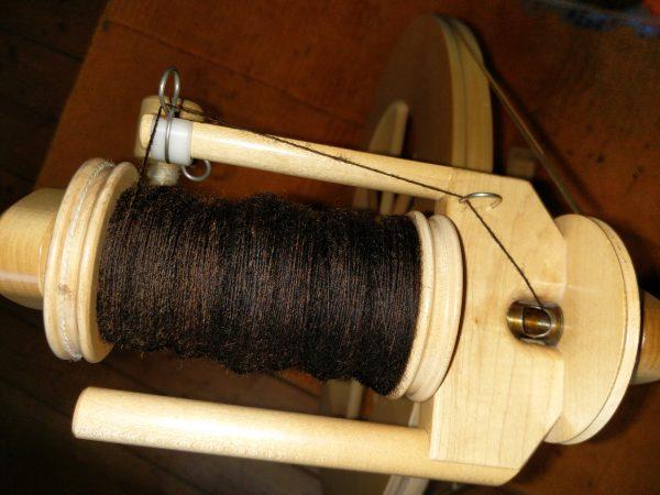 Spinnradspule mit brauner Wolle