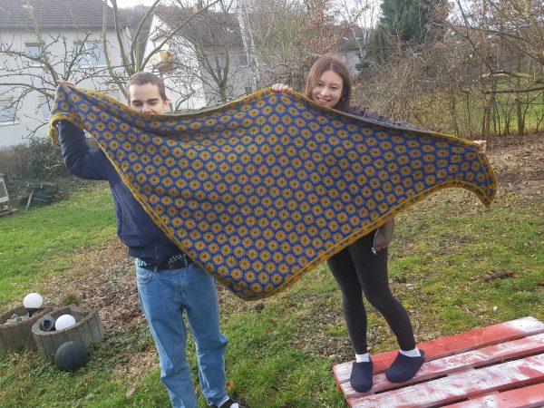 Ein Mann und eine Frau halten ein gestricktes gemustertes Tuch in blau-gelb auf einer Wiese