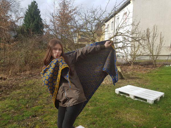 Eine junge Frau steht auf einer Wiese mit einem gemusterten Tuch
