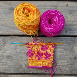 zwei Wollknaeuel in pink und orange und eine angefangener Sock auf buntem Nadelspiel